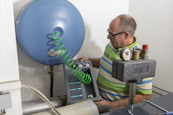 Ein Handwerker überprüft den Druck an einem Membran-Druckausdehnungsgefäß.