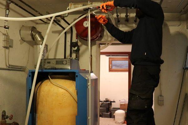Ein Handwerker arbeitet an der Verrohrung eines Heizkessels.