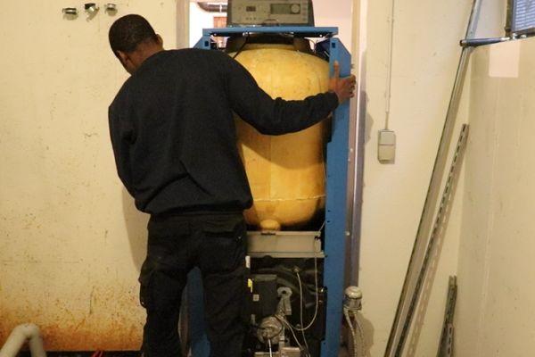 Ein Handwerker schiebt einen Heizkessel durch eine Kellertür.