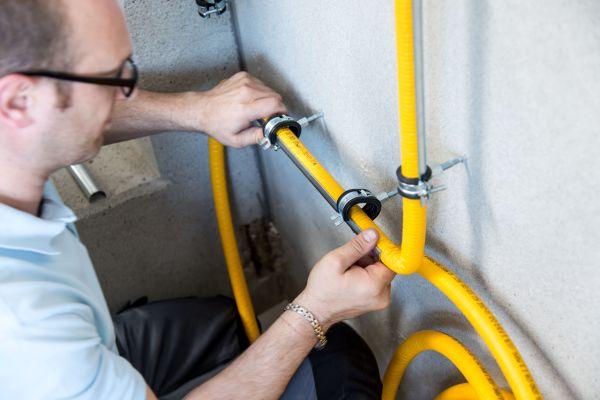 Ein Handwerker montiert Rohre an einer Wand.
