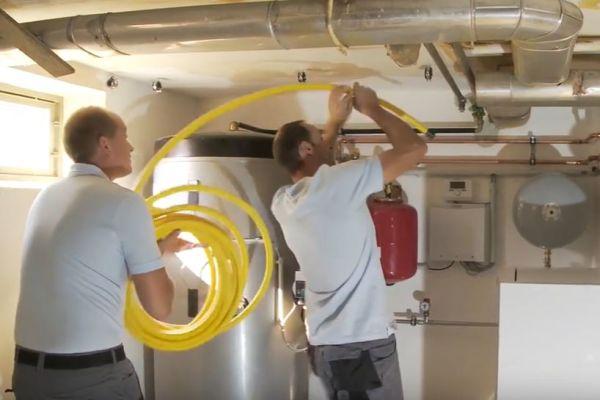 Zwei Handwerker montieren Rohre an einer Decke.