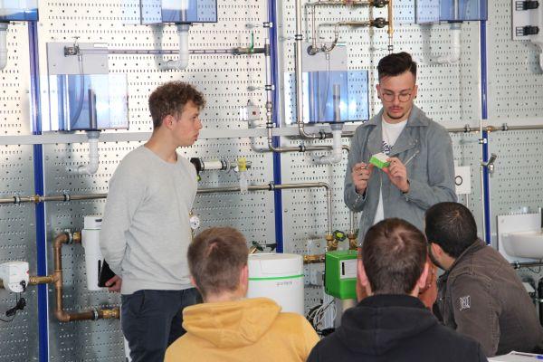 Zwei junge Männer nehmen eine Wasserprobe vor einem Modell einer Wasseraufbereitungsanlage.
