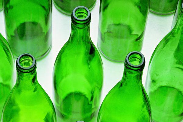 Das Bild zeigt leere Weinflaschen aus grünem Glas.