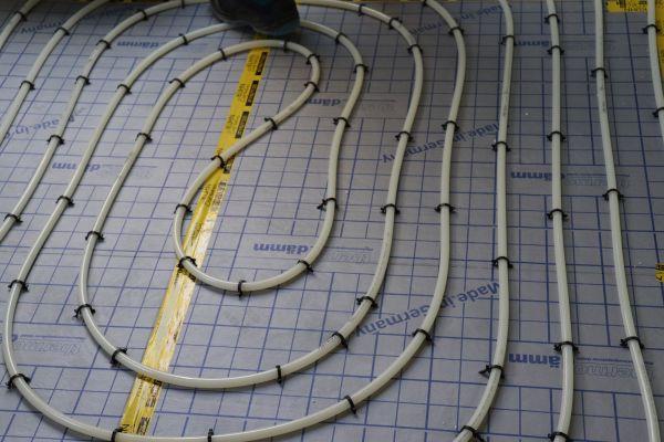 Rohre einer Fußbodenheizung auf einer Verlegeplatte.