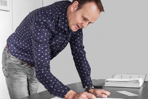 Ein Mann beugt sich über eine Zeichnung auf einem Tisch.