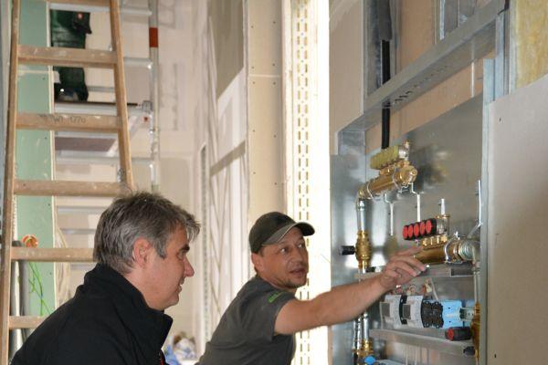 Zwei Handwerker knien vor einem Heizkreisverteiler.