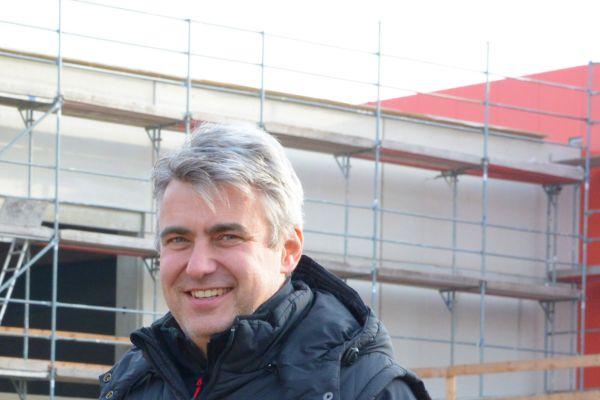 Ein Mann steht vor der Baustelle eines Hauses.