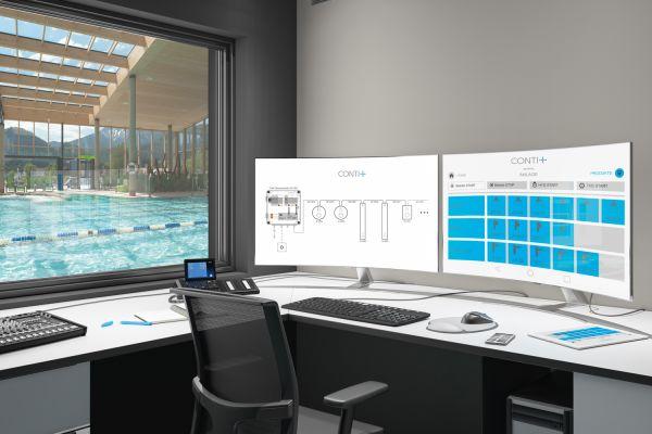 Ein Schreibtisch mit zwei Computerbildschirmen, aus dem Fenster sieht man auf ein Schwimmbecken.
