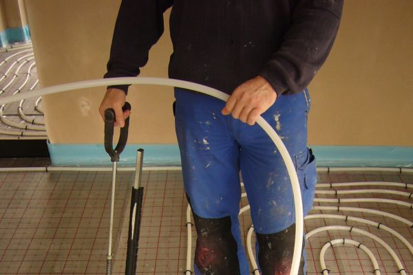 Installateur beim Verlegen von Fußbodenheizungs-Rohren.
