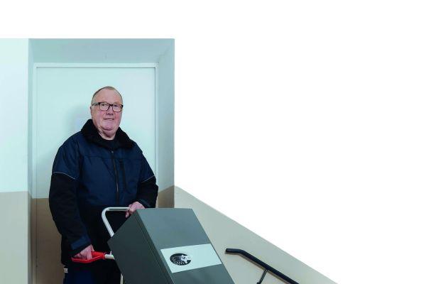 Ein Mann steht mit einer Sackkarre, auf der eine mobile Heizzentrale steht, in einem Treppenhaus.
