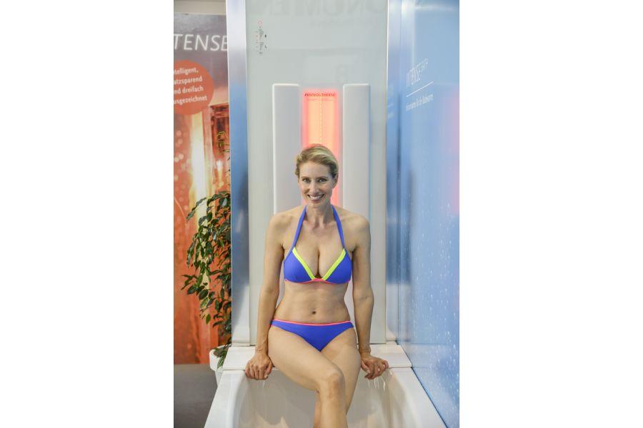 """Das Bild zeigt eine Frau im Bikini vor der Infrarot-Duschkabine """"Intense""""."""