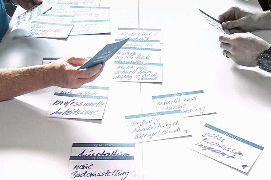 Das Bild zeigt beschrieben Zettel auf einem Tisch.