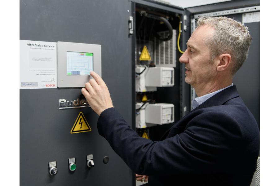 Hans Bretz bedient den Touchscreen der Modulsteuerung des Blockheizkraftwerks.