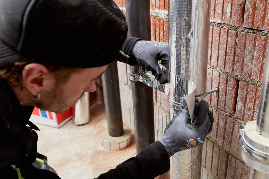 """Ein Handwerker verklebt einen Rundstoß zwischen den Rohrschalen mit """"Teclit Alutape""""."""