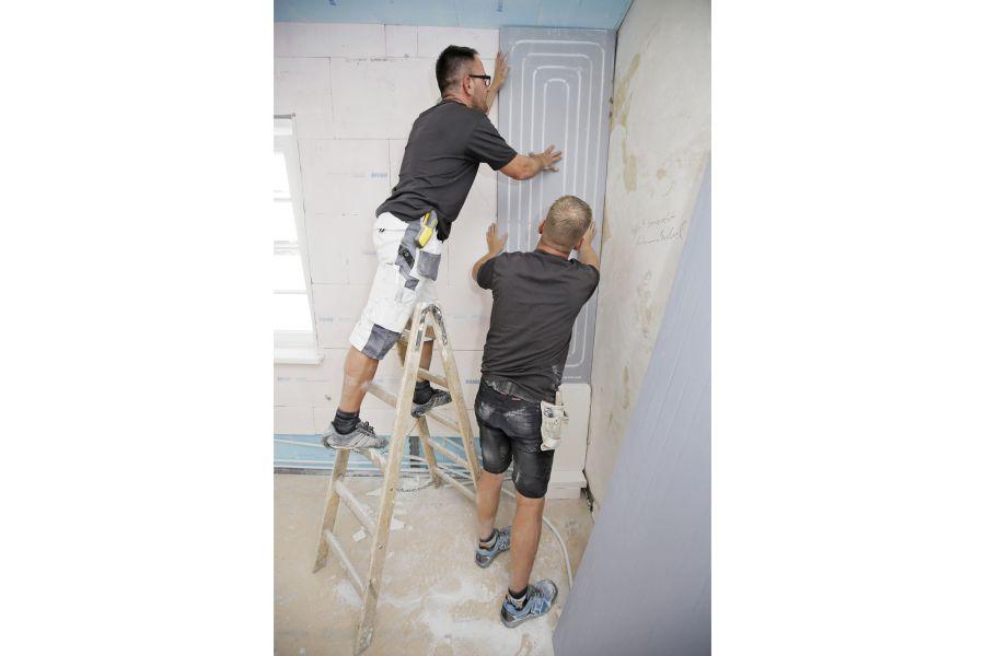 Handwerker montieren eine Dämmplatte einer Wandheizung.