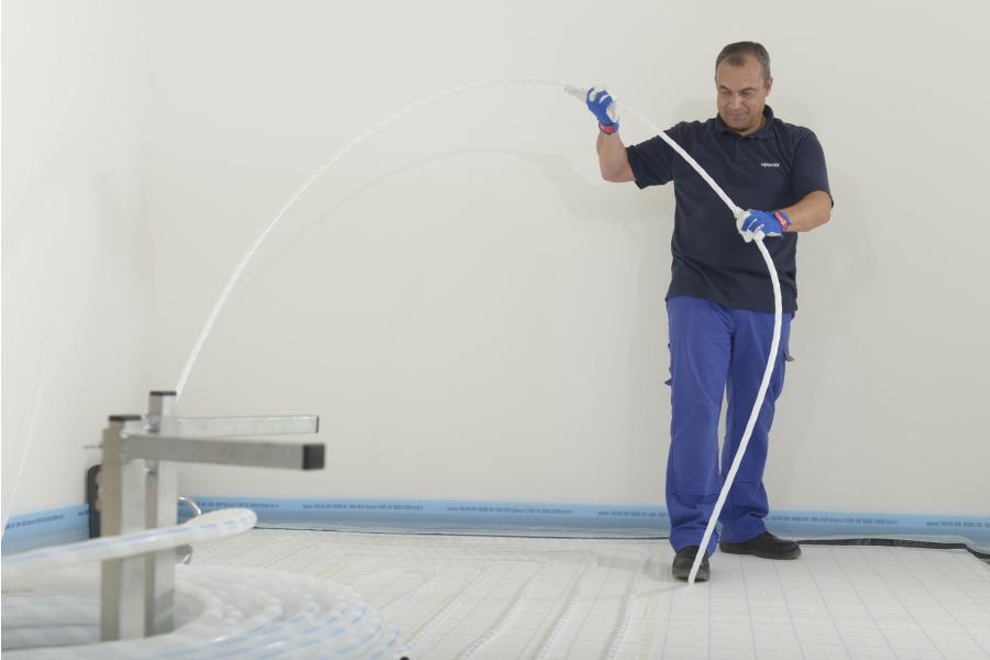 """Handwerker bei der Verlegung einer """"Klett""""-Fußbodenheizung."""
