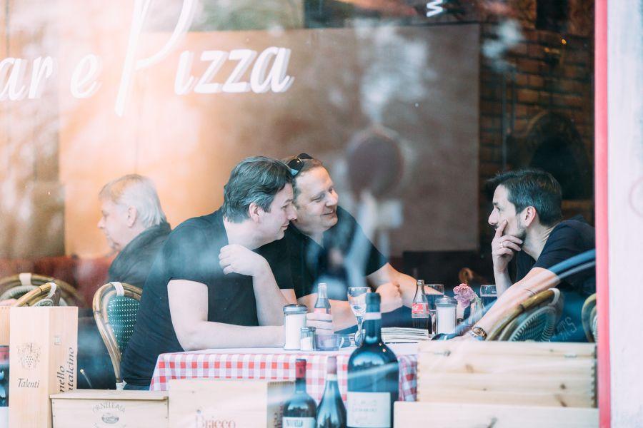 Andreas Lutzenberger, Helmut Schäffer und Christian Chymyn sitzen in einer Pizzeria.
