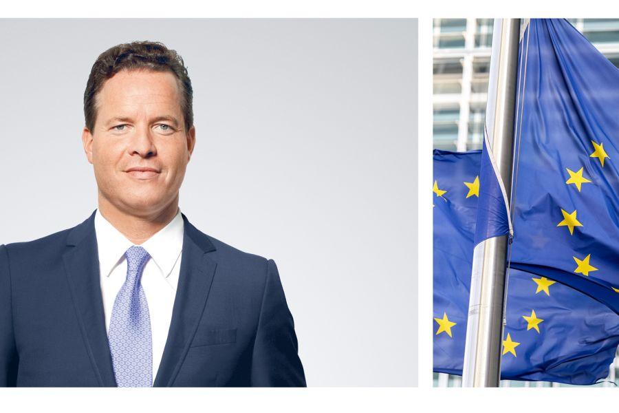 Das Bild zeigt Oliver Hermes (li.) und zwei Europafahnen (re.).