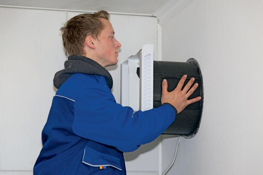 Ein Handwerker montiert das Einbaurohr für ein dezentrales Lüftungsgerät.