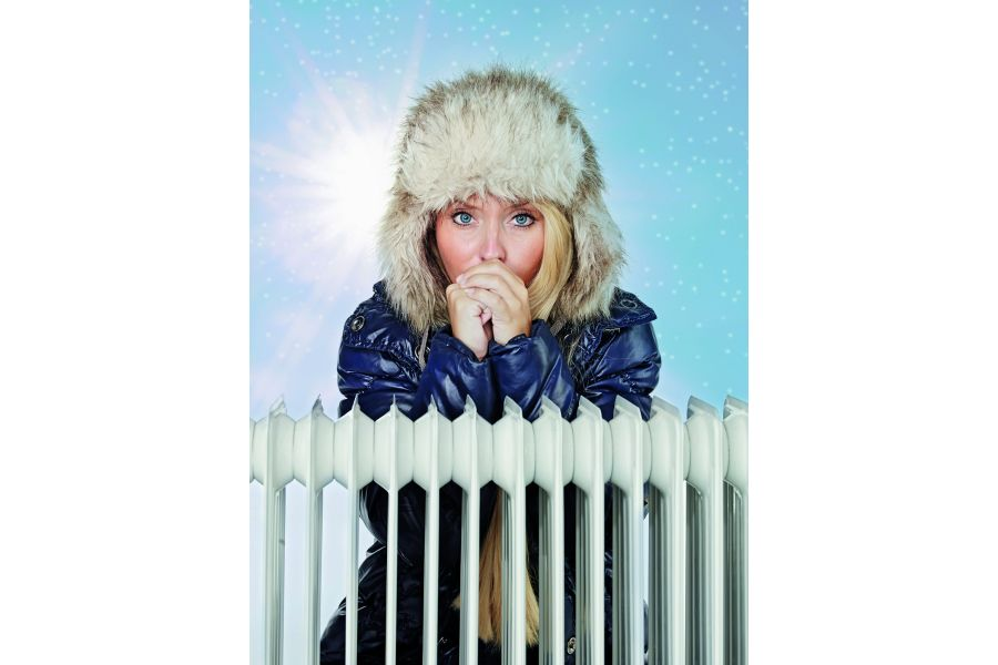 Eine Frau im Wintermantel steht hinter einem Heizkörper.