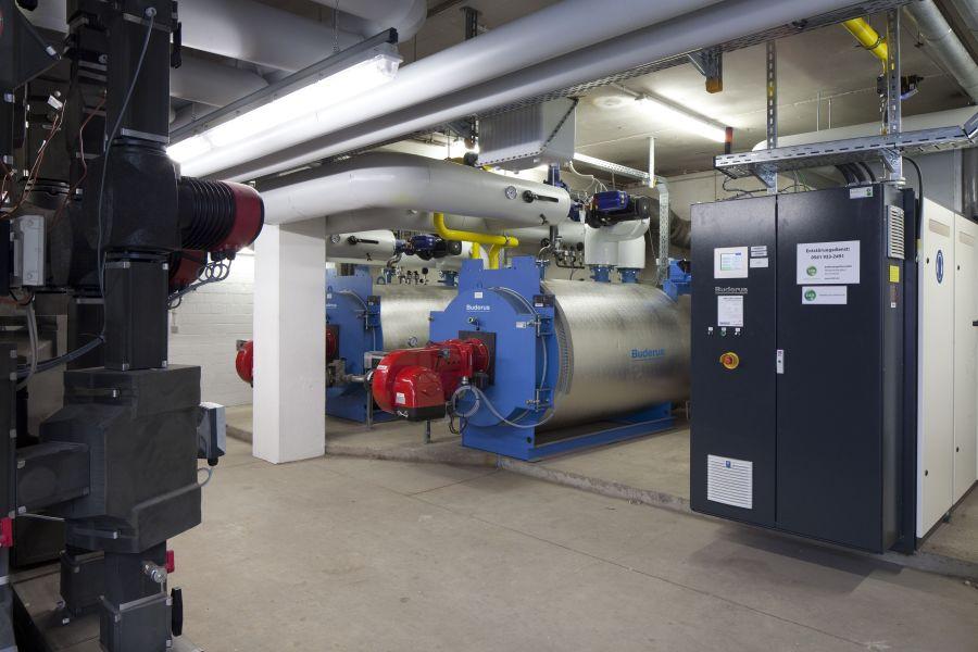 Zwei Niedertemperaturkessel und ein Blockheizkraftwerk in einem Heizungskeller.