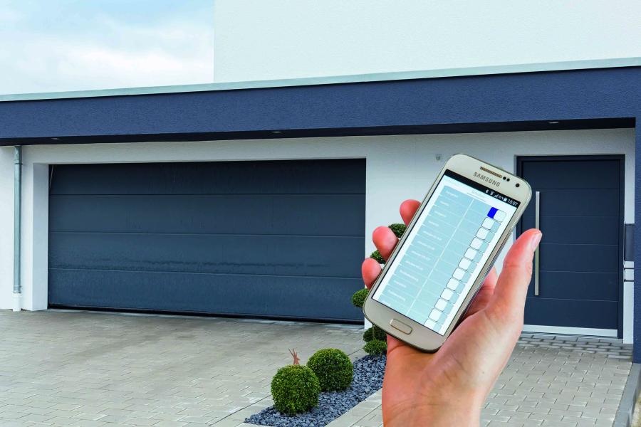 Eine Hand hält ein Smartphone vor ein Garagentor.