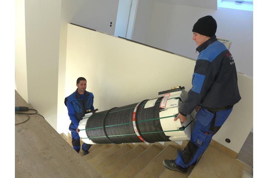 Zwei Handwerker tragen einen Kunststoff-Wärmetank eine Treppe hinauf.