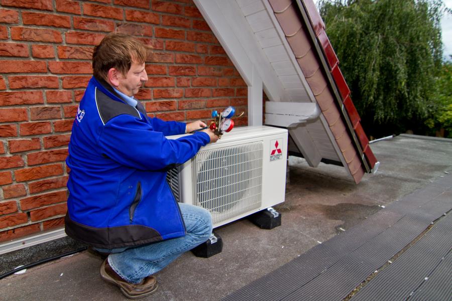 Ein Handwerker installiert außen an einem Haus ein Klimagerät.