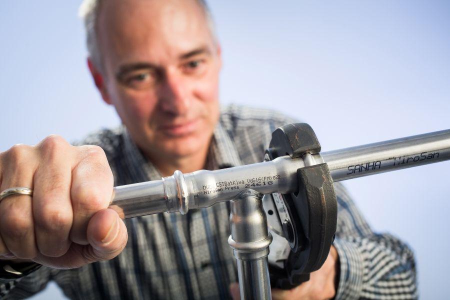 Ein Handwerker installiert ein Rohr.