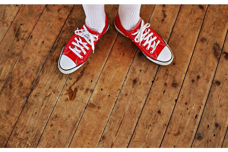 Ein paar Füße stehen auf einem Holzboden.