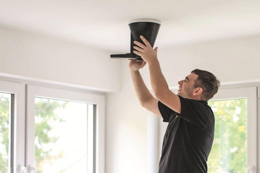 Ein Handwerker baut eine Kontrollierte Wohnungslüftung ein.