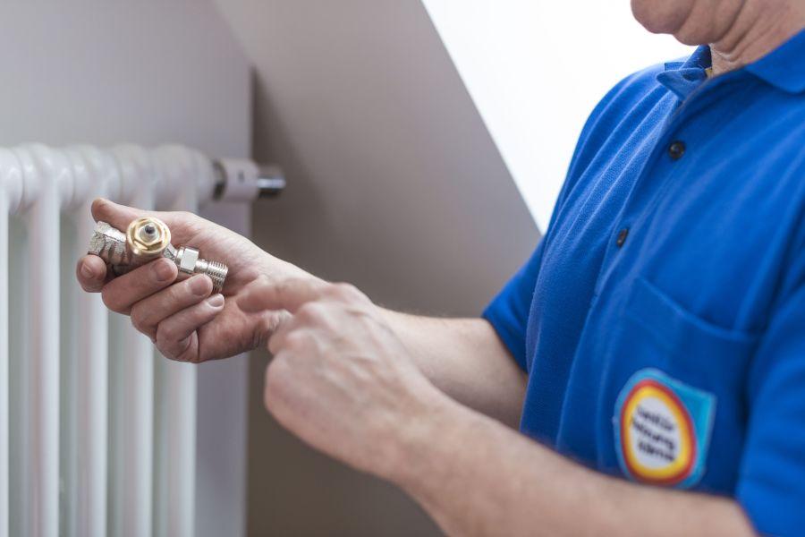 Ein Handwerker installiert ein neues Thermostatventil für einen Heizkörper.
