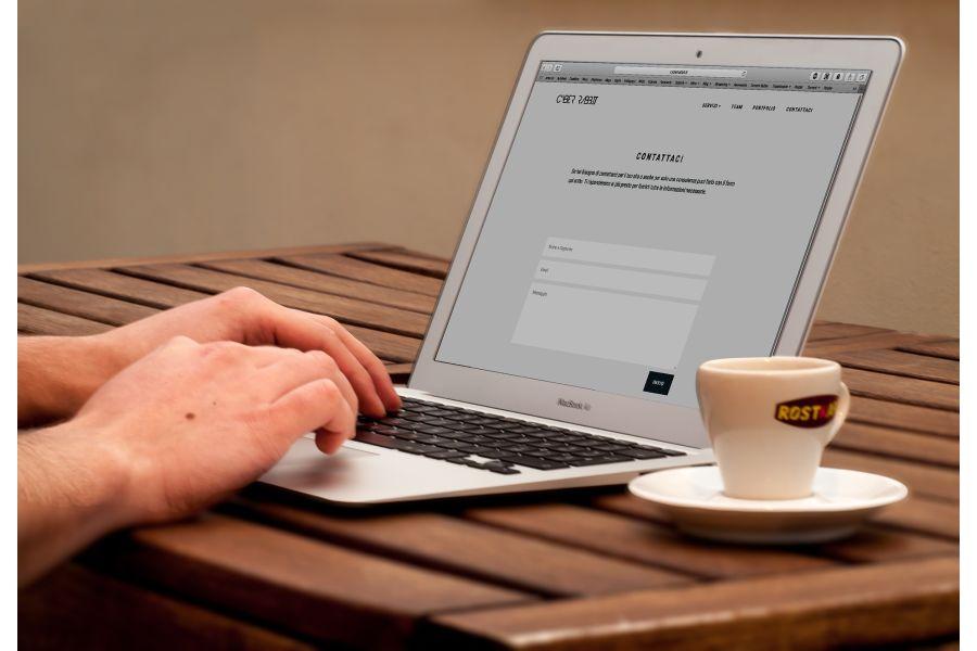 Eine Person tippt an einem Laptop, der auf einem Schreibtisch steht.
