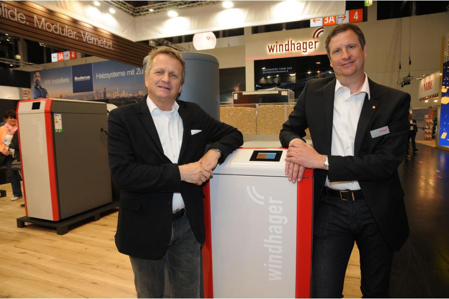 """Manfred Faustmann, Geschäftsführer der Windhager Zentralheizung GmbH, sowie Vertriebsleiter Frank Geißer vor dem neuen Pelletskessel """"BioWIN 2 plus"""" auf der IFH/Intherm 2018."""