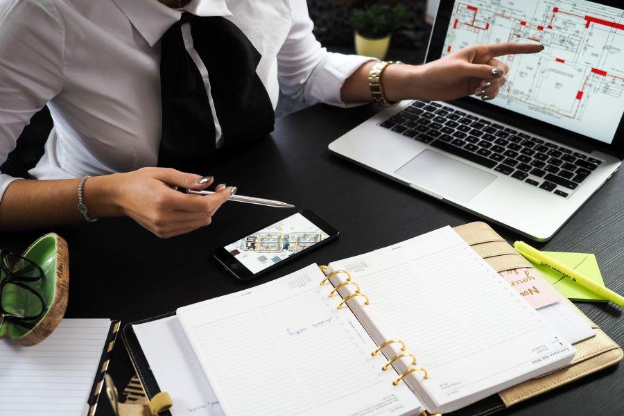Ein Architekt mit einem Plan auf einem Tisch und einem Plan auf einem Computerbildschirm.