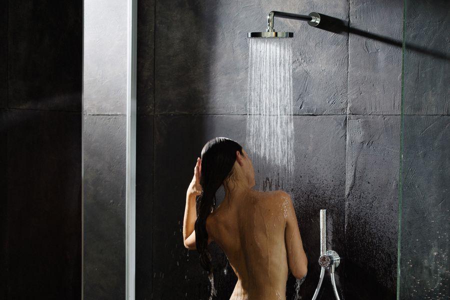 Das Bild zeigt eine Frau, die sich unter der Brause wäscht.Die Dusche ist mit den