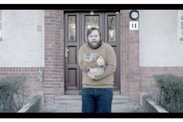 Ein Mann steht mit einer Katze auf dem Arm vor einer Haustür.