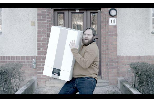 Ein Mann steht mit einer Therme auf dem Arm vor einer Haustür.