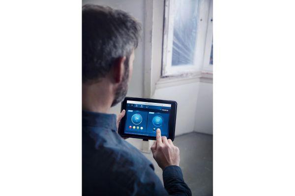 Ein Mann benutzt eine Buderus-App auf einem Tablet.