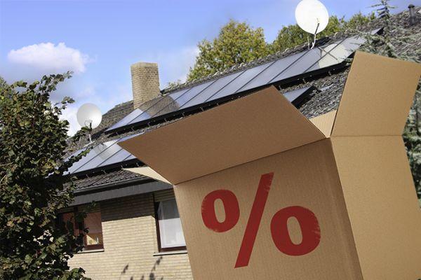 Ein Karton mit einem Prozentzeichen vor einem Haus mit Solaranlage.