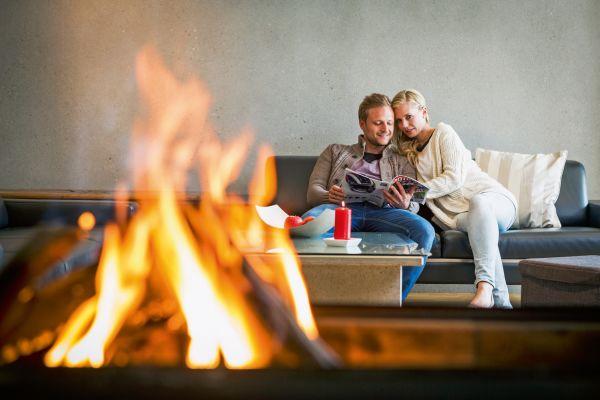 Ein Paar sitzt auf einem Sofa, im Vordergrund brennt ein Feuer.