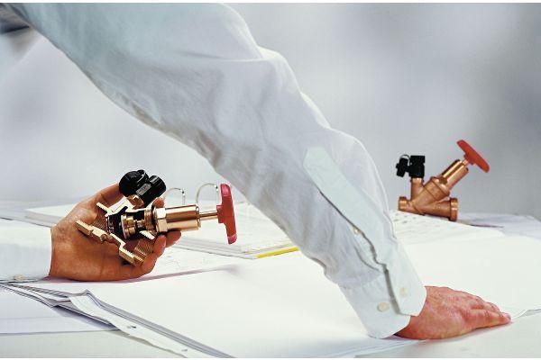 Ein Mann hält eine Absperrarmatur in der Hand.