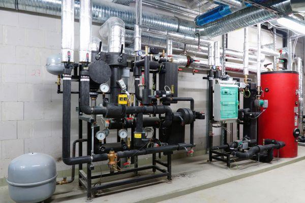 Fernwärmeübergabestation, Trinkwassererwärmungssystem und Pufferspeicher in einem Heizungskeller.