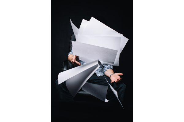 Ein Mann wirft einen Stapel Papier in die Luft.
