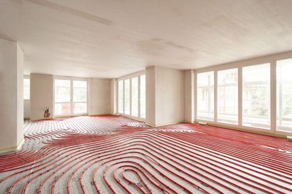 Die Rohre einer Fußbodenheizung in einem Raum.