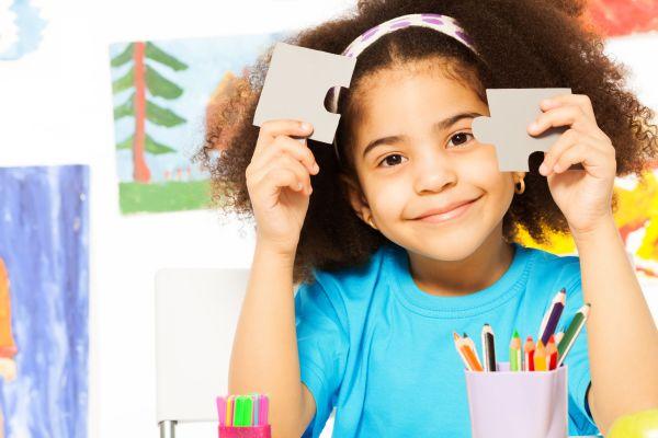 Ein Mädchen hält zwei Puzzleteile hoch.