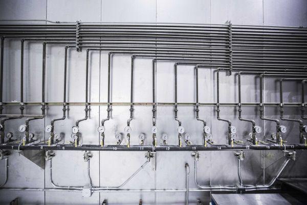 Ventile und Rohre an einer Wand.