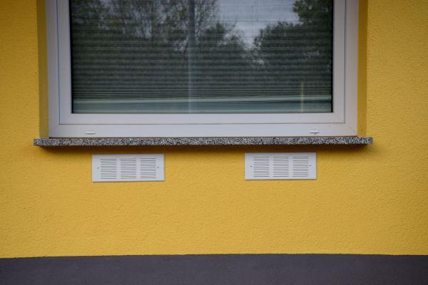 Ein Lüftungsgerät unter einem Fenster.