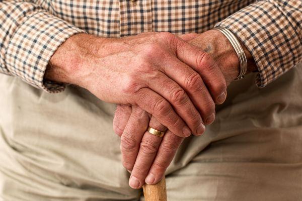 Ein Mann stützt sich mit beiden Händen auf einen Gehstock.