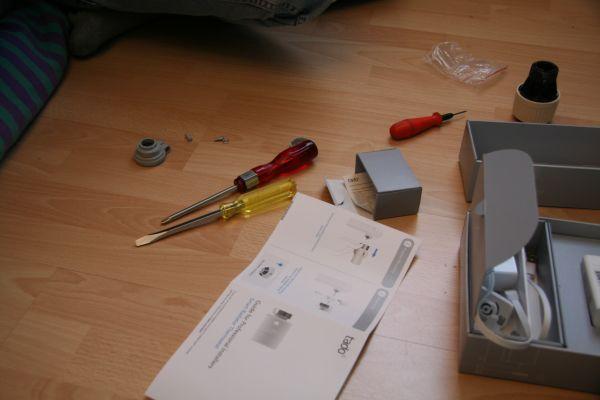 Eine Installationsanleitung für smarte Heizkörper-Thermostate liegt neben einem Schraubenzieher auf dem Boden.